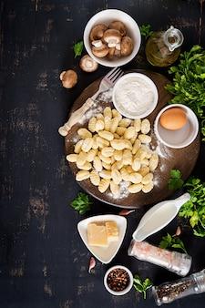 Nhoque caseiro cru com molho de creme de cogumelos e salsa na tigela sobre uma mesa escura.