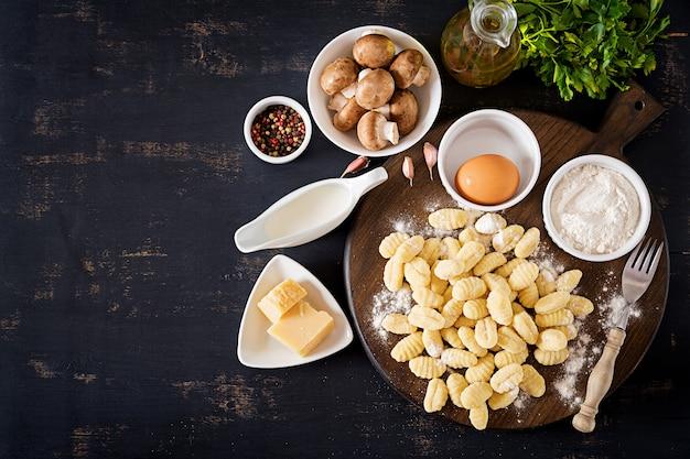 Nhoque caseiro cru com um molho de creme de cogumelos e salsa na tigela