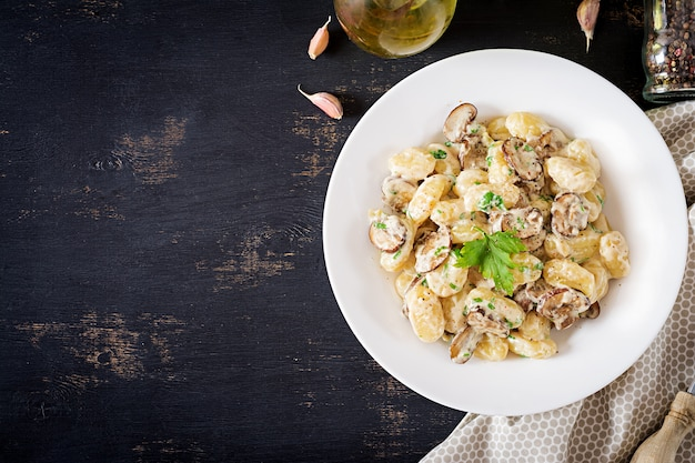 Nhoque com molho de creme de cogumelos e salsa na tigela sobre um fundo escuro.