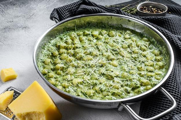 Nhoque com molho de espinafre e manjericão. pasta de batata italiana. fundo cinza. vista do topo.