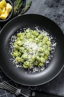 Nhoque com molho de espinafre e manjericão. pasta de batata italiana. fundo preto. vista do topo