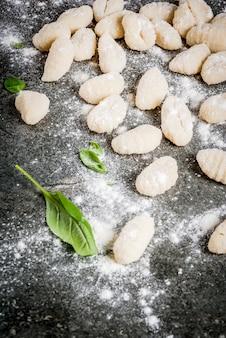 Nhoque de batata caseiro cru cru com farinha, queijo parmesão ralado, manjericão e molho pesto. no concreto cinza,