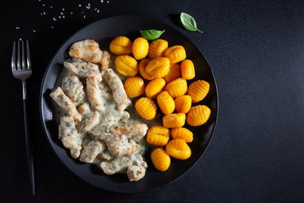 Nhoque de batata doce com frango ao molho servido na chapa escura em fundo escuro.