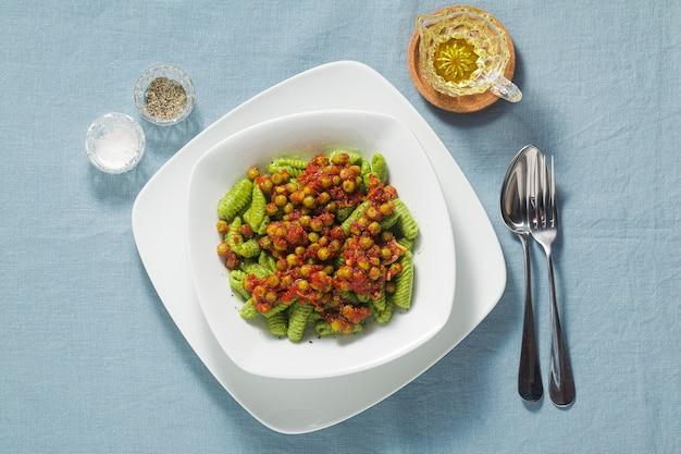 Nhoque italiano de massa fresca tradicional da sardenha com espinafre e molho de tomate ervilha. macarrão da primavera para as férias da páscoa.