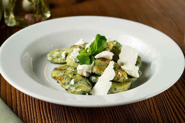 Nhoque verde com manjericão, espinafre, queijo pesto feta em composição com pano verde e azeite de oliva.