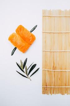 Nigiri salmão japonês com esteira de sushi e folha de oliveira com fundo branco