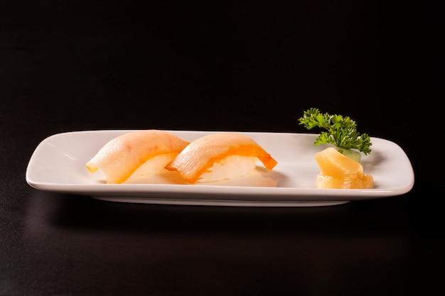 Nigiri shiromi sushi com peixe salmão em fundo preto