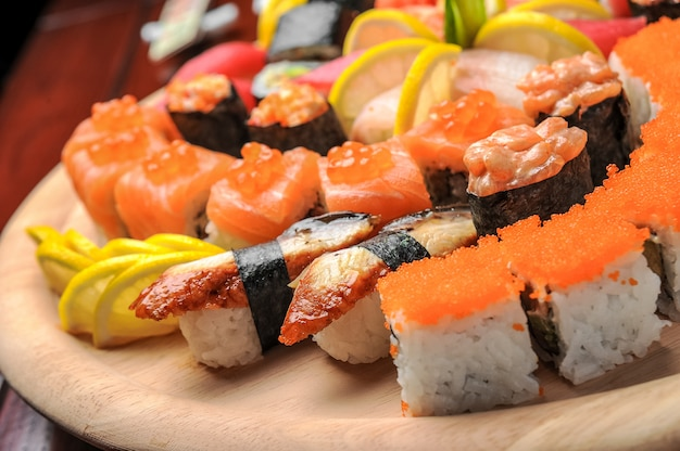 Nigiri sushi e pãezinhos com peixe servido na mesa de madeira