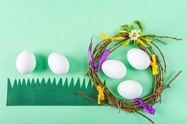 Ninho de artesanato caseiro de galhos e fitas coloridas com ovos brancos na superfície verde. configuração de mesa de páscoa. composição festiva de páscoa com espaço de cópia para o texto.
