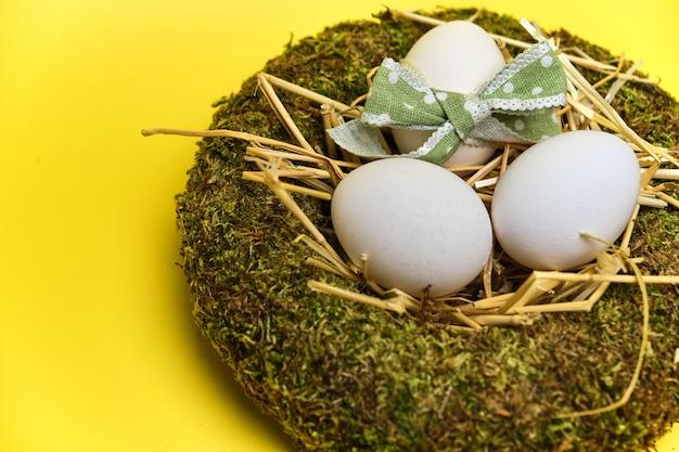 Ninho de cesta de páscoa com ovos de páscoa em fundo amarelo