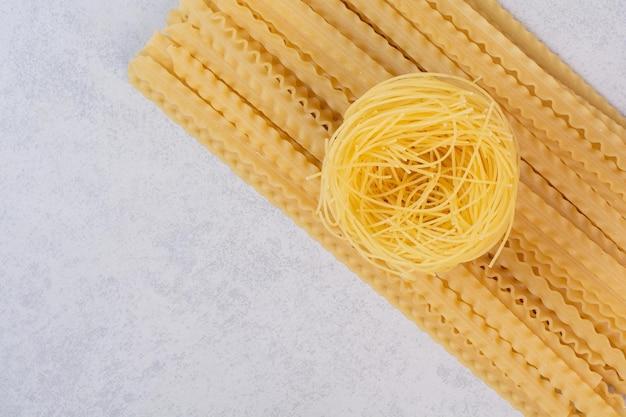 Ninho de espaguete cru e macarrão na mesa de mármore.