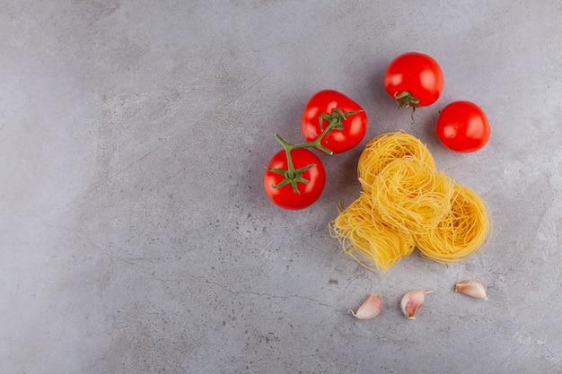 Ninho de fettuccine de massa italiana com tomates vermelhos frescos e especiarias.