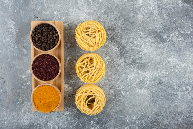 Ninho de macarrão cru com especiarias em uma mesa cinza.