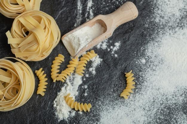 Ninho de macarrão cru com farinha no preto.