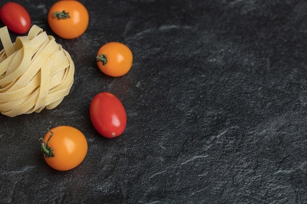 Ninho de macarrão cru com tomate cereja no preto.