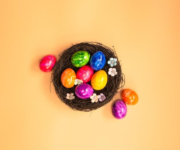 Ninho de ovo de páscoa pintado de colorido com vista superior de fundo laranja em tons pastéis, fundo de conceito de feliz páscoa holliday