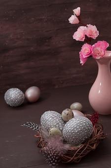 Ninho de páscoa com ovos em fundo marrom com flores de flor rosa baixa ainda vida