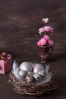 Ninho de páscoa com ovos em fundo marrom com flores rosa e caixa de presente