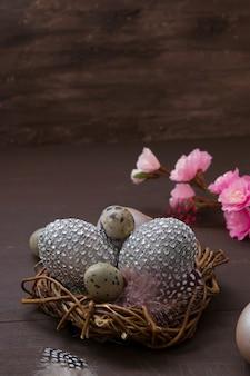 Ninho de páscoa feliz com ovos em um fundo marrom com flores cor de rosa e uma caixa de presente.