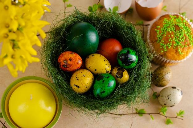 Ninho de páscoa verde com muitos ovos coloridos diferentes
