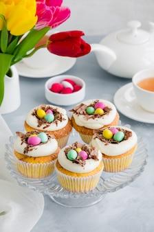 Ninho de pássaro de cupcakes de baunilha de páscoa com ovos de creme, chocolate e doces