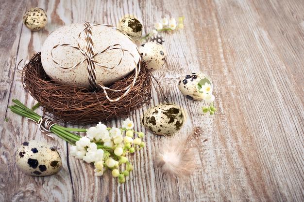 Ninho de pássaro, ovos e lírio do vale na madeira