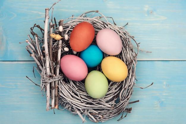 Ninho de pássaro preenchido com ovos de cor pastel