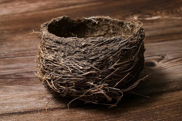 Ninho de pássaro real vazio isolado na mesa de madeira.
