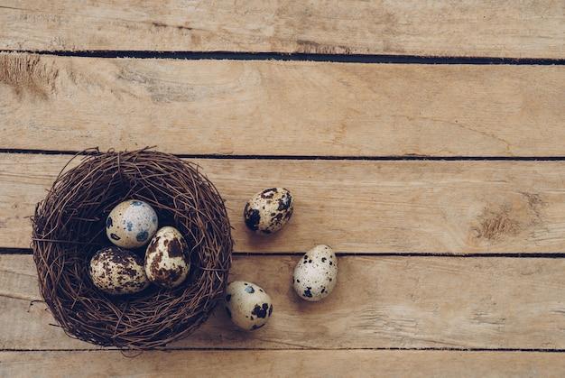 Ninho e ovos da páscoa de madeira no fundo e na textura de madeira com espaço da cópia.