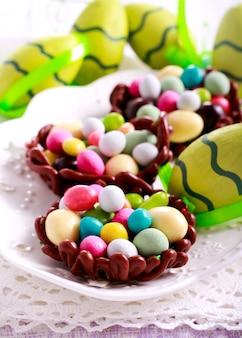 Ninhos de chocolate cheios de doces em forma de ovo para a páscoa,