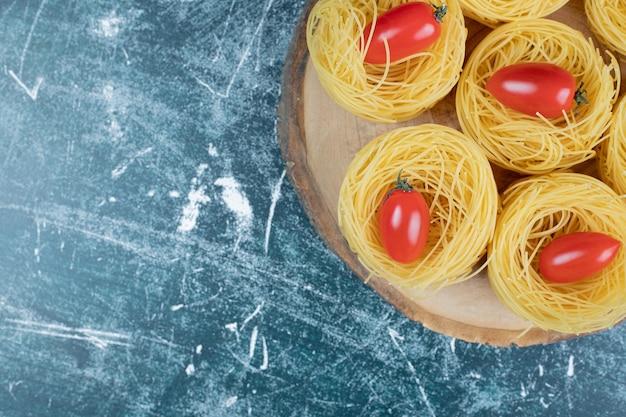 Ninhos de espaguete cru com tomates na placa de madeira.