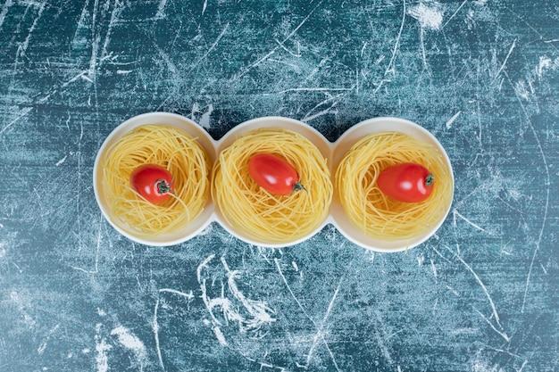 Ninhos de espaguete cru com tomates no espaço azul.