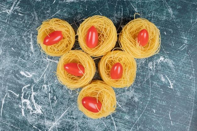 Ninhos de espaguete cru e tomate sobre fundo azul. foto de alta qualidade
