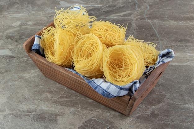 Ninhos de espaguete cru em caixa de madeira