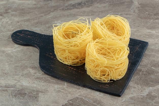 Ninhos de espaguete finos na placa de madeira.