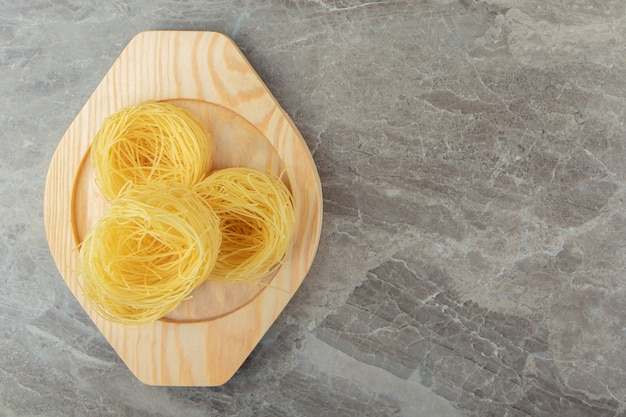 Ninhos de macarrão cru em placa de madeira