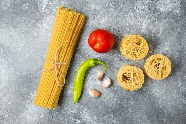 Ninhos de massa crua de tagliatelle, espaguete e vegetais na superfície de mármore.