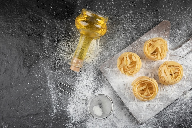 Ninhos de tagliatelle fresco cru com uma placa de madeira com uma garrafa de óleo
