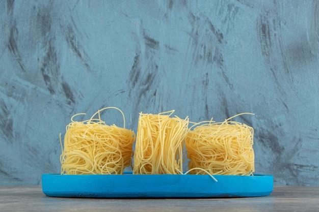 Ninhos finos de espaguete em prato azul