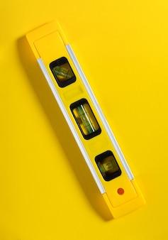 Nível de construção em um fundo amarelo. uma ferramenta indispensável para o mestre construtor