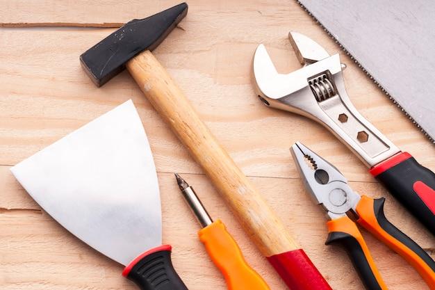 Nível, espátula, chave de fenda, martelo, alicate, chave ajustável, serra. conjunto de ferramentas de construção em um fundo de concreto.