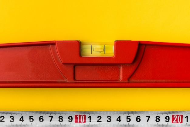 Nível vermelho do edifício e fita métrica em fundo amarelo.