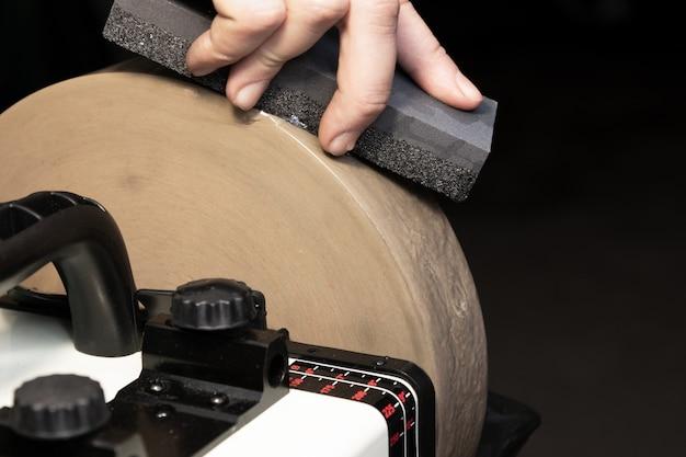 Nivelamento da pedra de moagem com uma lâmina para afiar facas.