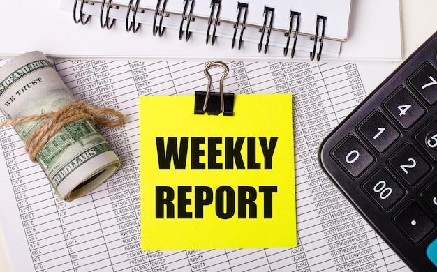 No ambiente de trabalho encontram-se relatórios, blocos de notas, uma calculadora, um dinheiro e um autocolante amarelo com o texto relatório semanal. conceito de negócios