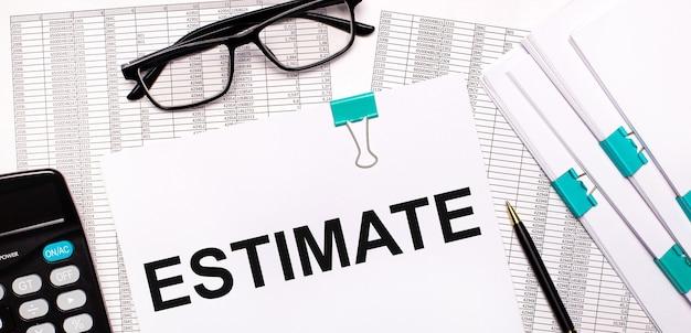 No ambiente de trabalho encontram-se relatórios, documentos, óculos, uma calculadora, uma caneta e papel com o texto estimativa. conceito de negócios