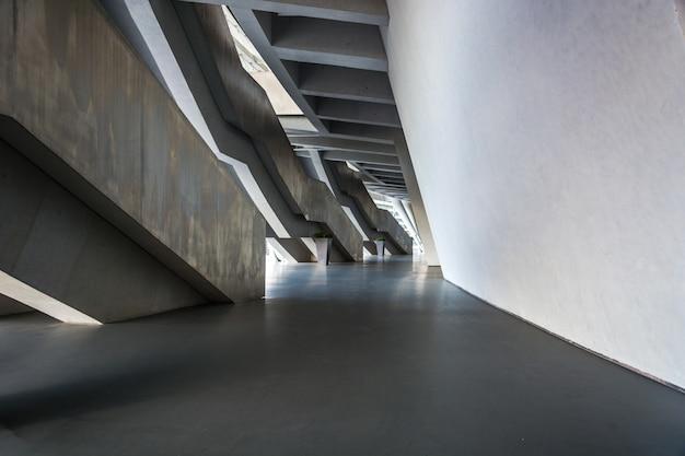 No andar de cima, com corrimãos metálicos pendurados no ar no meio da parede de tijolos de pedra à luz do sol