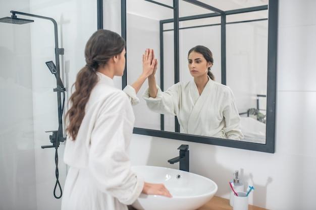 No banheiro. uma jovem de cabelos escuros em um roupão de banho branco no banheiro