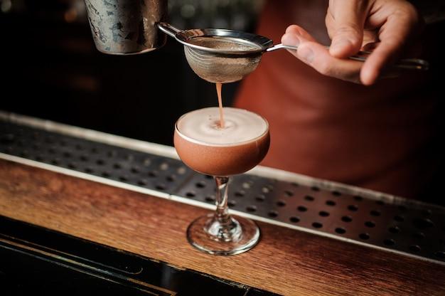 No barman rosto derramando cocktail em vidro