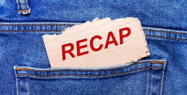 No bolso de trás da calça jeans há um pedaço de papel marrom com o texto recap.