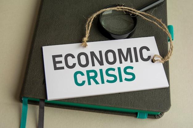 No caderno cinza está uma lupa e um cartão de papel branco com a inscrição crise econômica, foco seletivo